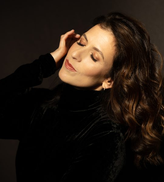 Inbal Segev wears a black velvet top and rests her hand against her face with her eyes closed and her hair flowing behind her.