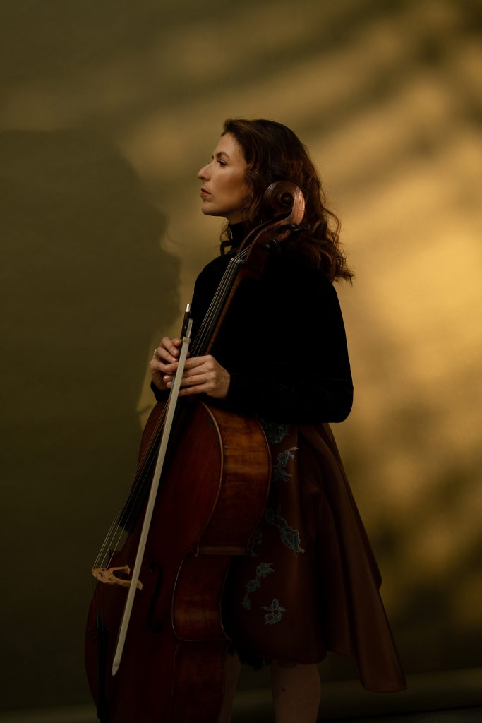 Inbal Segev stands against a light brown background, wearing a brown skirt with a blue flower pattern and a black top, while looking to the side and holding her cello.