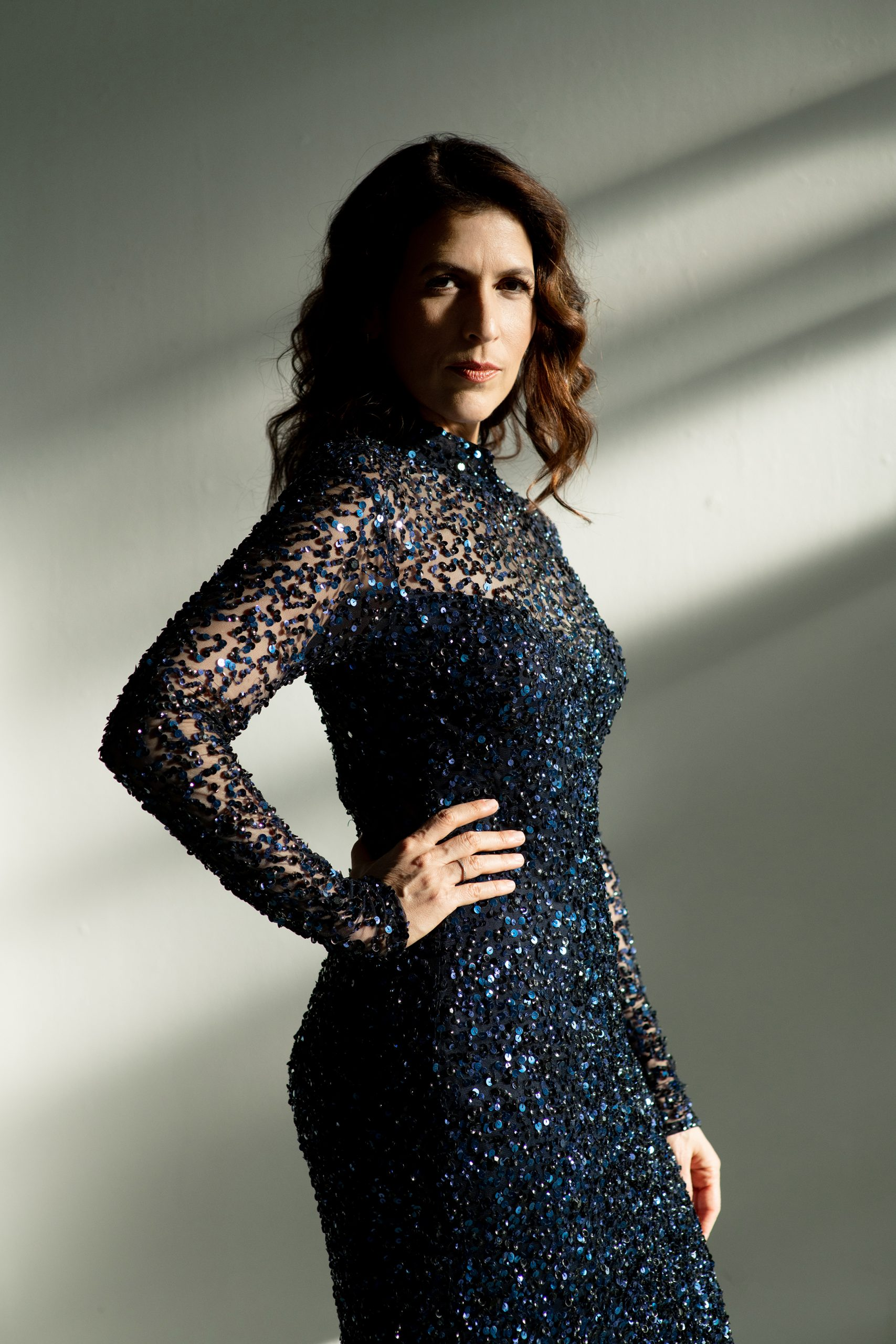Inbal Segev stands against a white and grey background wearing a blue sequined dress, looking serious with her hand on her hip.