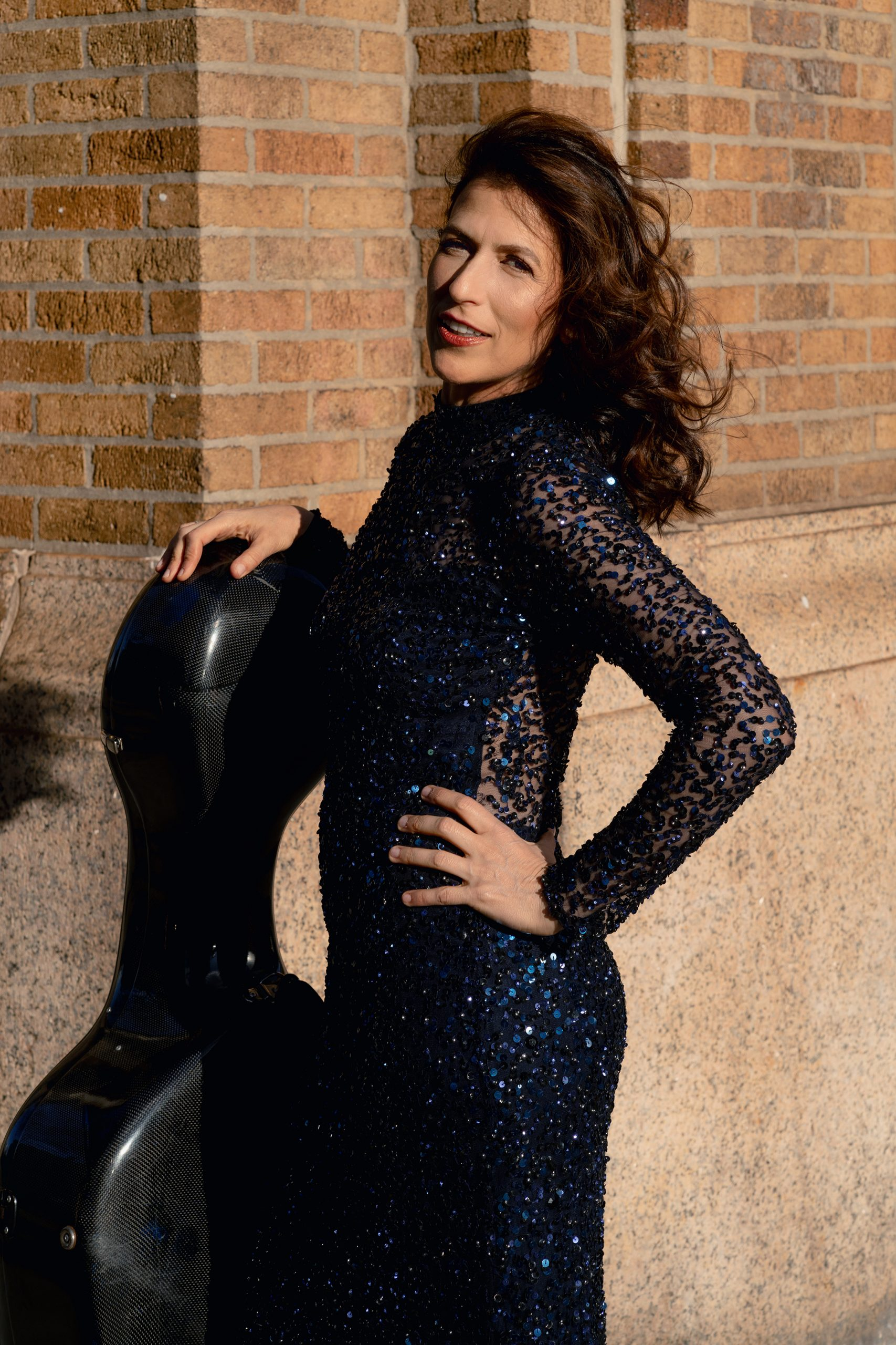 Inbal Segev stands in front of a brick wall wearing a blue sequined gown, with her cello case leaning against her.