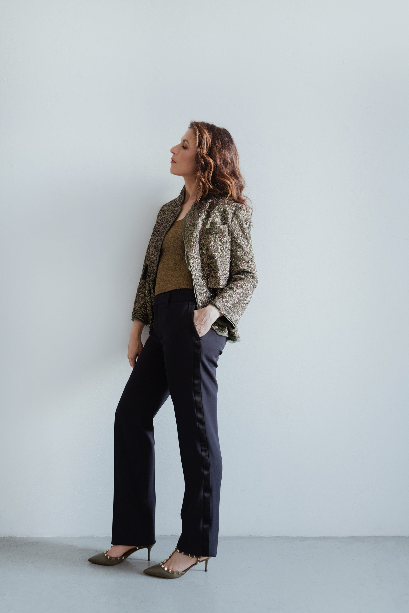 Inbal Segev leans against a while wall wearing dark pants, and a brown patterned blazer.