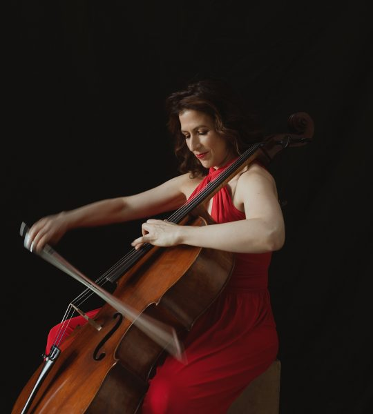Inbal Segev, in a flowing red gown, sits on a chair and plays her cello.