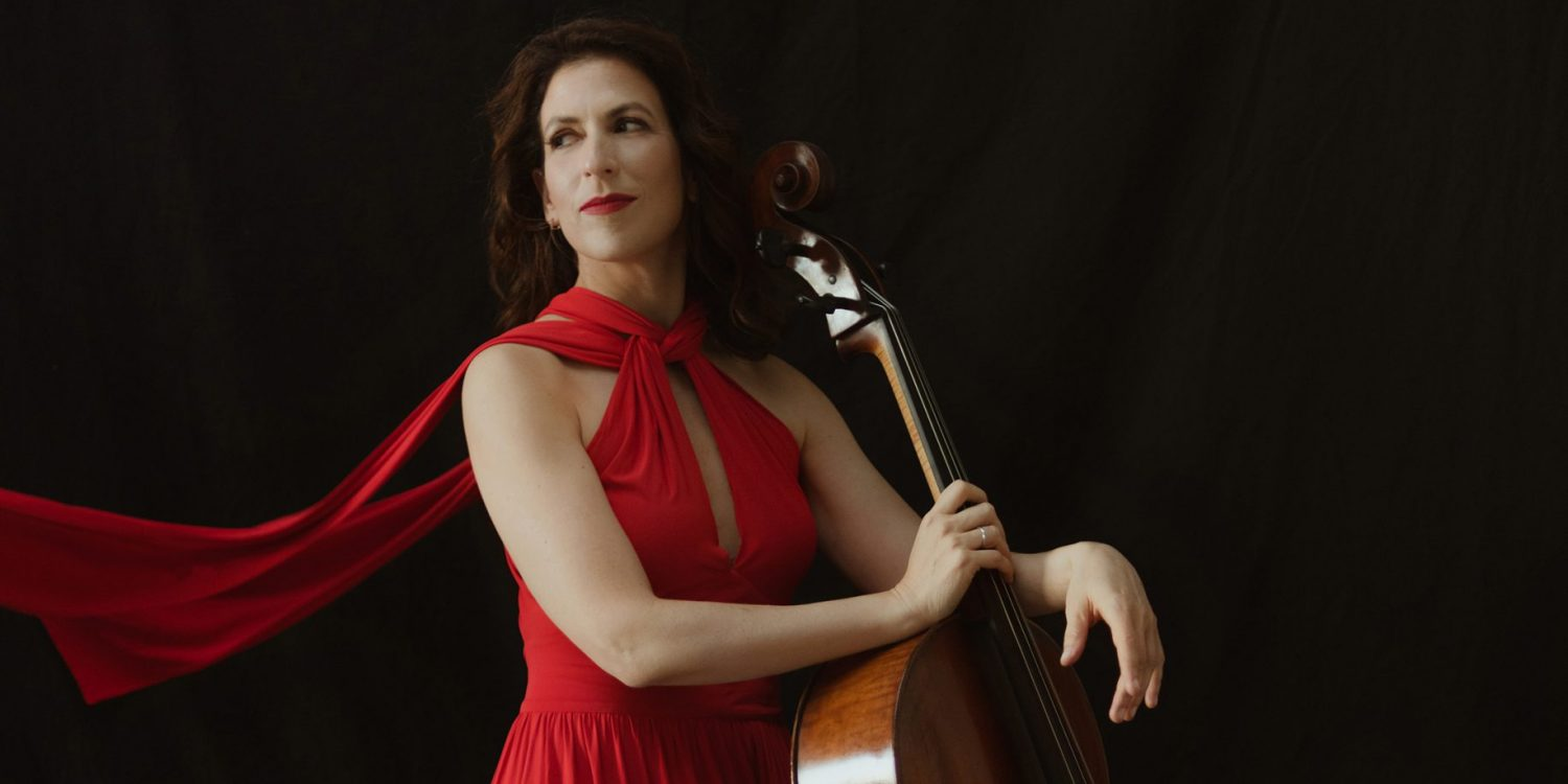 Inbal Segev stands against a dark backdrop wearing a flowing red gown and resting her cello against her side.