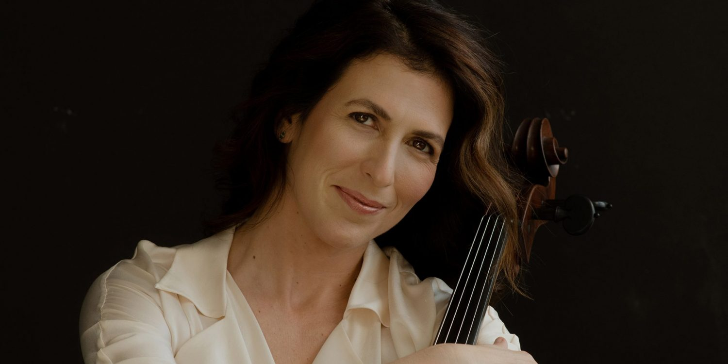 Inbal Segev hugs her cello and smiles, wearing a white blouse against a black background.