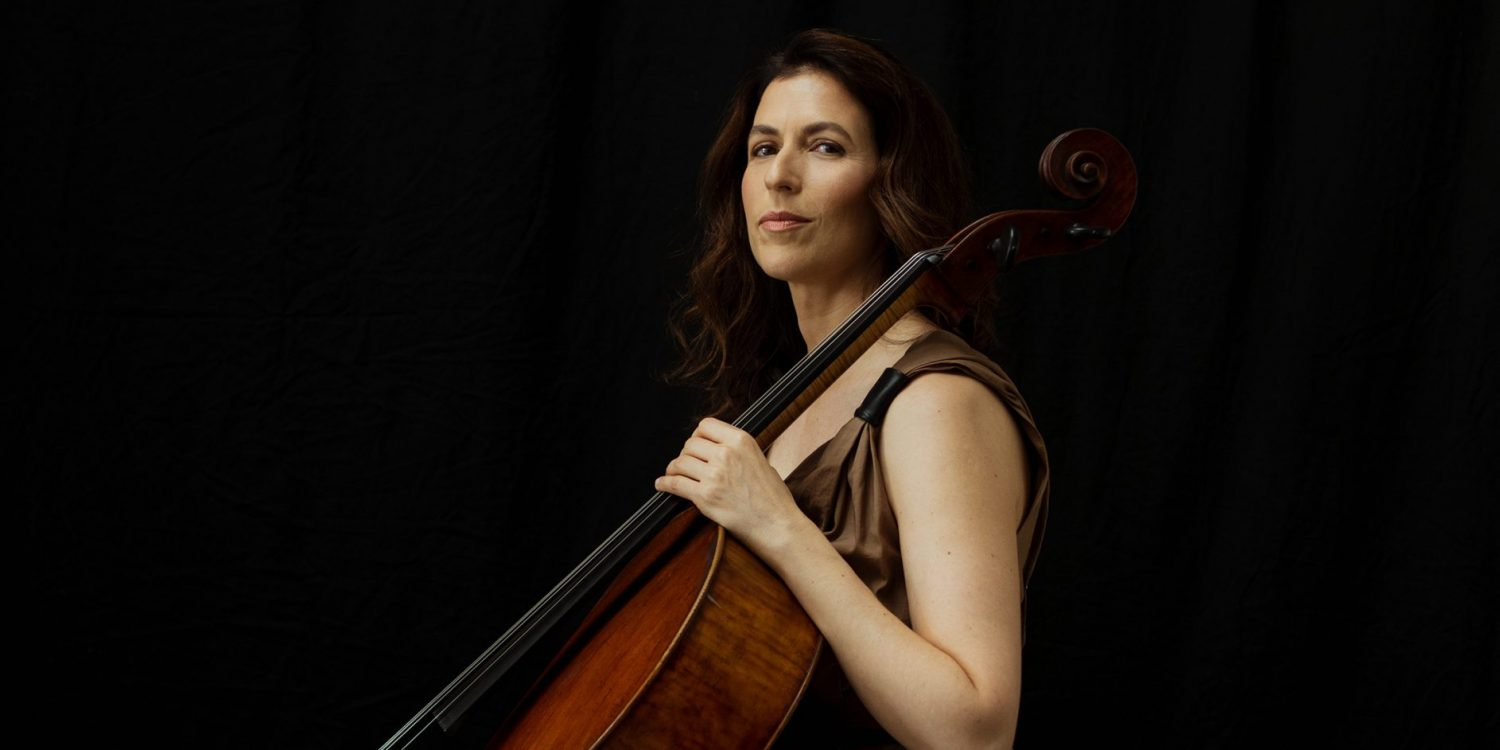 Inbal Segev sits on a stool holding her cello and bow, wearing a sleeveless loose brown dress and looking serious.