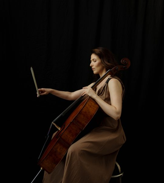 Inbal Segev sits on a stool, playing her cello in a loose, sleeveless brown dress against a black background.