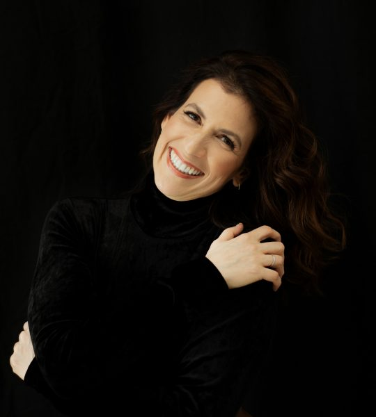 Inbal Segev against a black background wearing a black velvet top and smiling with her arms hugging her shoulders.