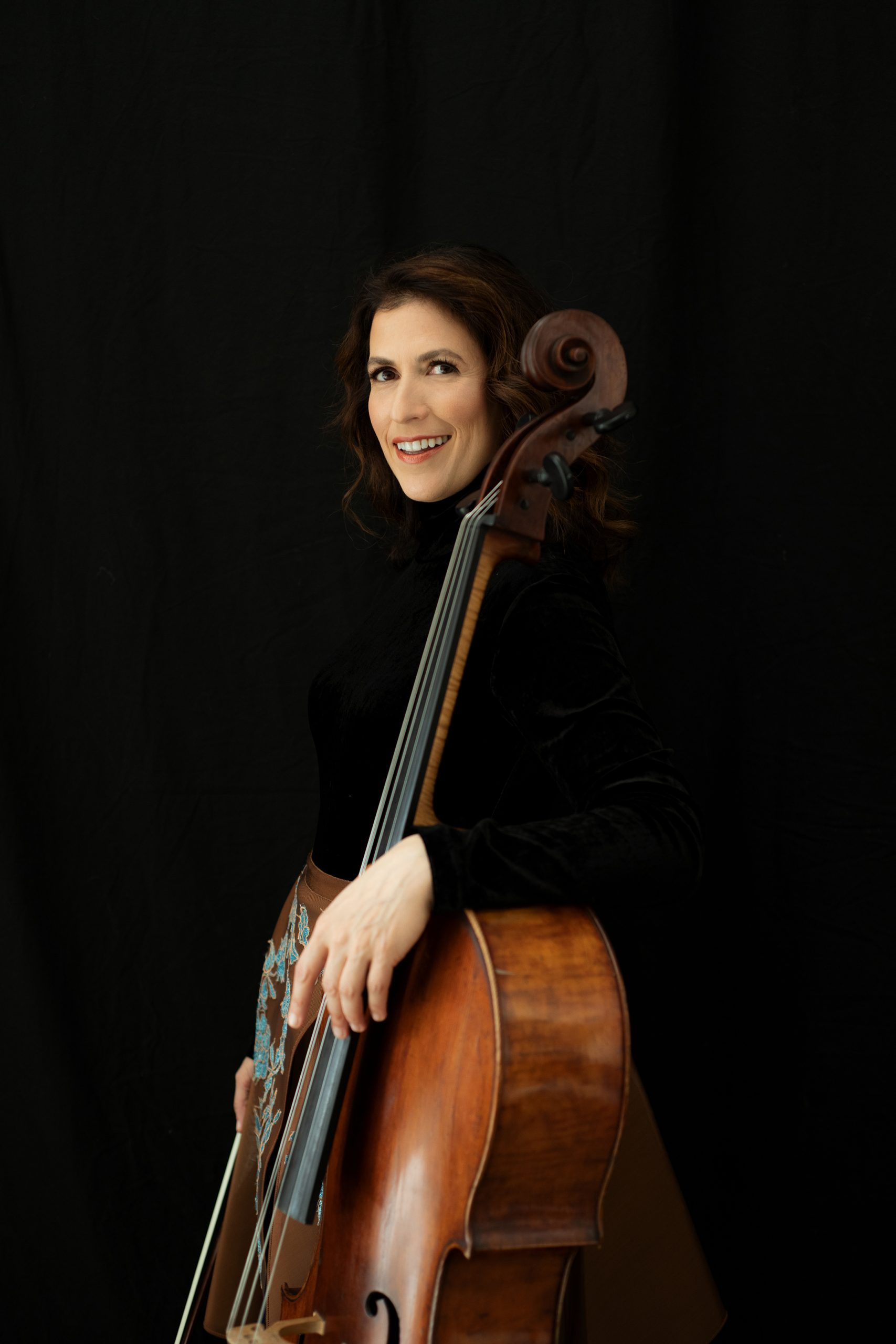 Inbal Segev stands with her cello against a black background smiling and wearing a black top and a brown skirt with a blue flower pattern.