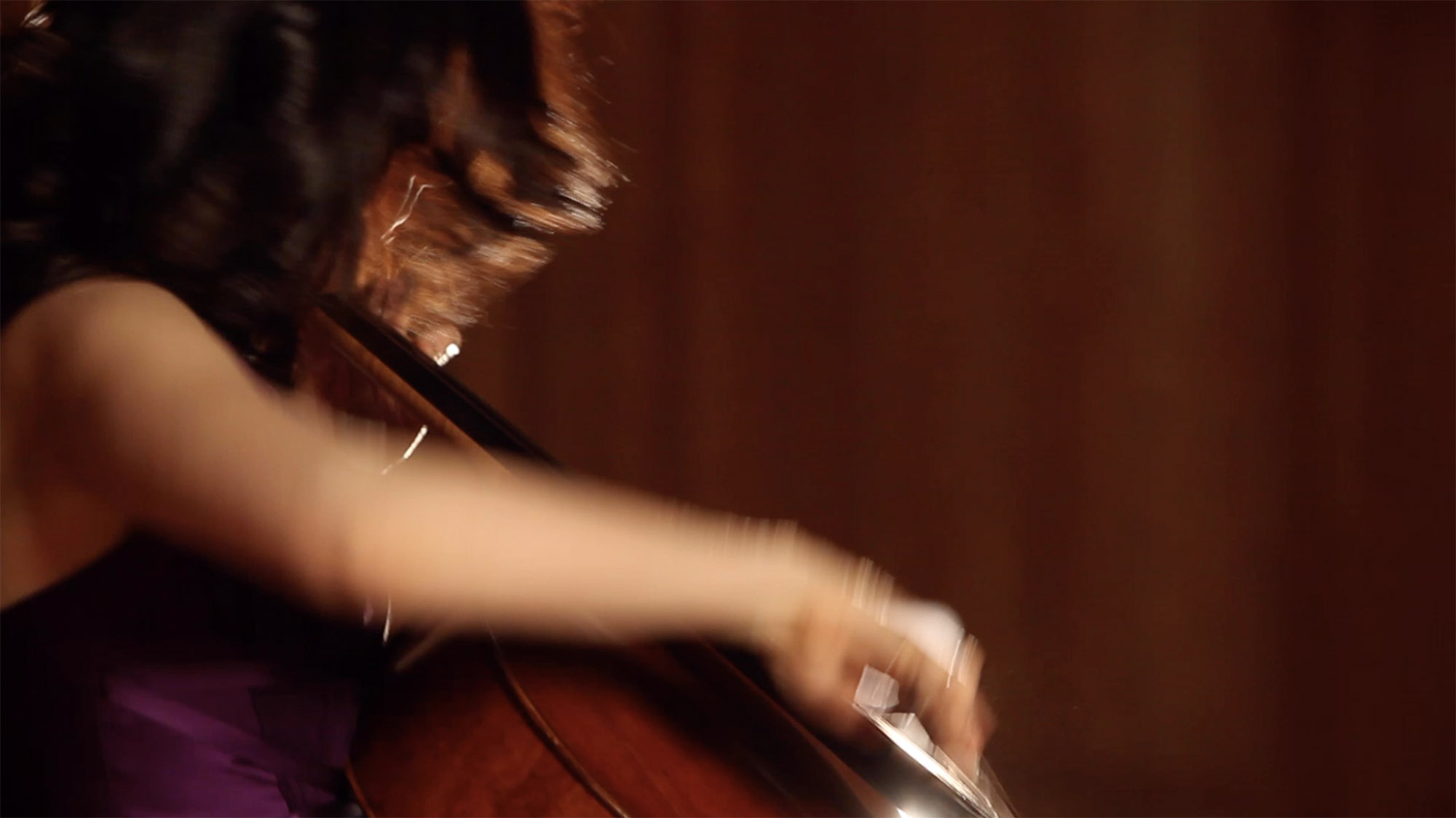 A blurry shot of Inbal Segev playing cello while sitting down and wearing a purple top.